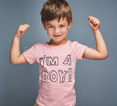 "Buy stock photo Studio portrait of a cheering boy wearing a shirt with ""I'm a boy"" printed on it against a grey background"