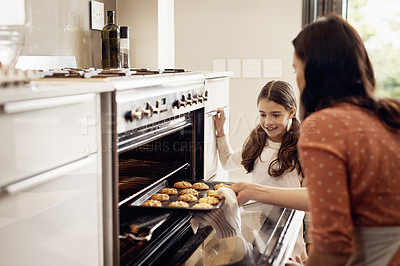 Buy stock photo Shot of a little girl and her mother removing freshly baked cookies out of the oven