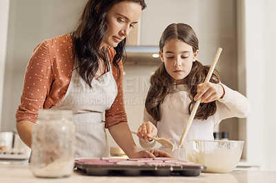Buy stock photo Shot of a young girl and her mother baking in their kitchen at home