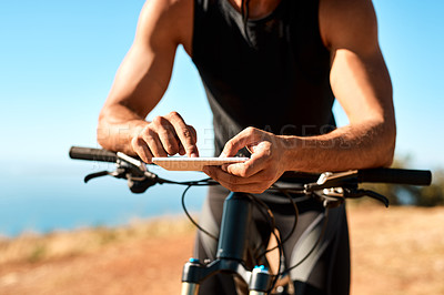 Buy stock photo Cropped shot of an unrecognizable man using his cellphone while out for a ride on his mountain bike