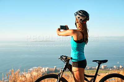 Buy stock photo Cropped shot of a young woman taking a picture of the beautiful scenery while out mountain biking