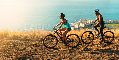 Buy stock photo High angle shot of a happy young couple out mountain biking together