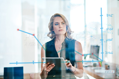 Buy stock photo Shot of a young businesswoman using a digital tablet while analyzing graphs on a glass wall in an office