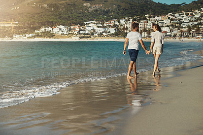 Buy stock photo Rearview shot of a carefree young couple walking hand in hand along the beach