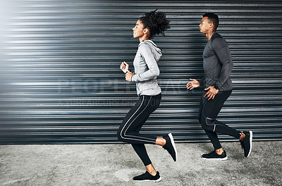 Buy stock photo Shot of a sporty young couple running against a grey background