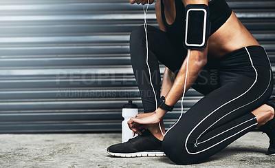 Buy stock photo Closeup shot of a sporty woman tying her shoelaces while exercising against a grey background