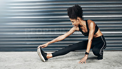 Buy stock photo Shot of a sporty young woman stretching her legs against a grey background
