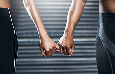 Buy stock photo Closeup shot of a sporty couple holding each other's little finger against a grey background