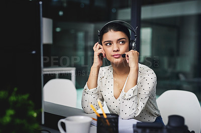 Buy stock photo Cropped shot of an attractive young businesswoman looking bored while working late in a call center