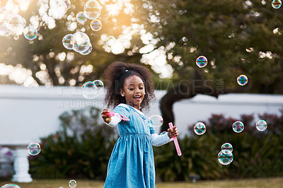 Buy stock photo Shot of an adorable little girl playing with bubbles outdoors