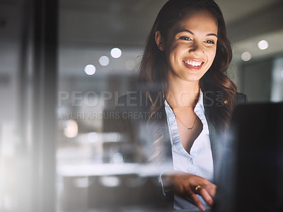 Buy stock photo Cropped shot of an attractive young businesswoman using her laptop while working late in the office
