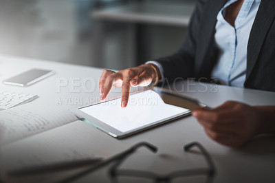 Buy stock photo Cropped shot of an unrecognizable young businesswoman using her tablet to shop online while working late in the office