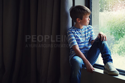 Buy stock photo Shot of a sad young boy watching the rain through a window at home