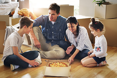 Buy stock photo Shot of a happy young family having pizza together in their new home