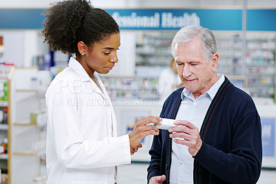 Buy stock photo Shot of a young pharmacist recommending a health care product to a senior citizen at a pharmacy