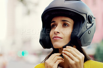 Buy stock photo Closeup shot of an attractive young woman putting on her helmet in the city
