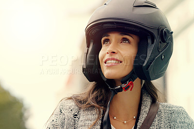 Buy stock photo Closeup shot of an attractive young woman wearing a helmet and riding her scooter through the city