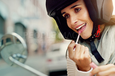 Buy stock photo Closeup shot of an attractive young woman putting on lipstick while wearing a helmet in the city