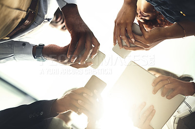 Buy stock photo Closeup shot of a group of businesspeople using their digital devices in synchronicity in an office