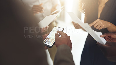 Buy stock photo Shot of a group of businesspeople using digital devices and going through paperwork in an office