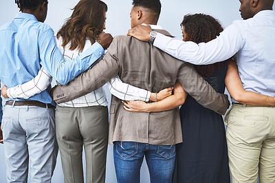 Buy stock photo Rearview studio shot of a group of businesspeople embracing against a gray background