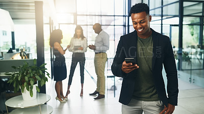 Buy stock photo Shot of a young businessman using a cellphone in an office with his colleagues in the background