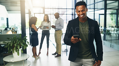 Buy stock photo Portrait of a young businessman using a cellphone in an office with his colleagues in the background