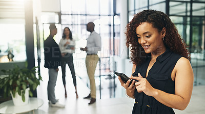 Buy stock photo Shot of a young businesswoman using a cellphone in an office with her colleagues in the background