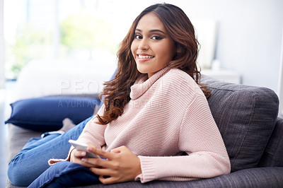 Buy stock photo Shot of a young woman using a mobile phone while relaxing at home