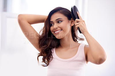 Buy stock photo Shot of an attractive young woman brushing her hair in the bathroom at home