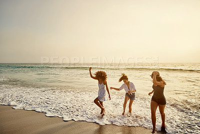 Buy stock photo Shot of a group of friends spending time together at the beach