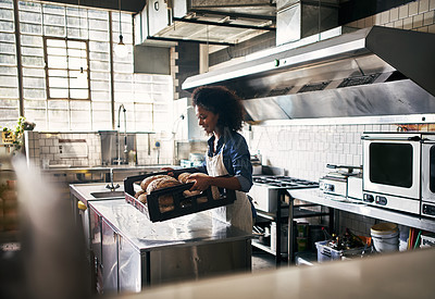Buy stock photo Cropped shot of an attractive young woman working in the kitchen in her coffee shop