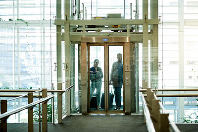 Buy stock photo Shot of two businesspeople using an elevator in an airport
