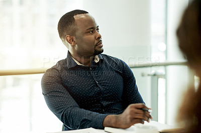 Buy stock photo Cropped shot of a handsome young businessman sitting in the boardroom during a meeting