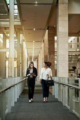 Buy stock photo Shot of two businesswomen having a discussion while walking in a modern office