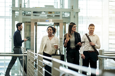 Buy stock photo Shot of a group of businesspeople having a discussion while walking through a convention center during a business trip