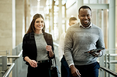 Buy stock photo Shot of two businesspeople walking in a modern office
