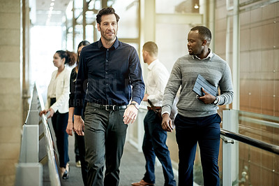 Buy stock photo Shot of a group of businesspeople walking in a modern office