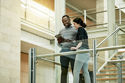 Buy stock photo Shot of two businesspeople using a digital tablet together in a modern office