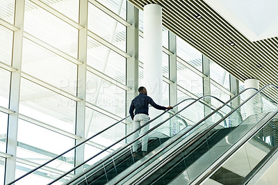 Buy stock photo Rearview shot of an unrecognizable businessman on an escalator in the workplace