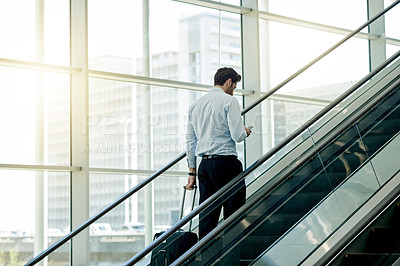 Buy stock photo Rearview shot of an unrecognizable businessman using a cellphone while on an escalator in the workplace