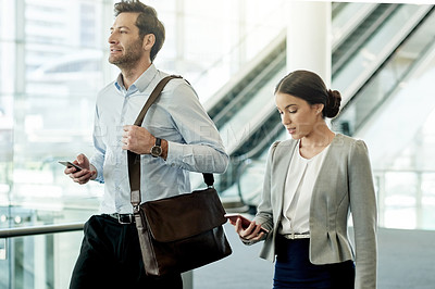 Buy stock photo Cropped shot of two businesspeople using their cellphones while walking together