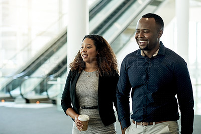 Buy stock photo Shot of two businesspeople having a conversation while walking together