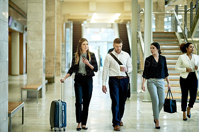 Buy stock photo Shot of a group of businesspeople walking through a convention center while on a business trip