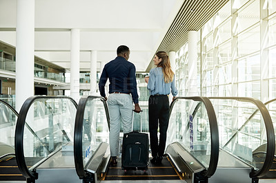 Buy stock photo Rearview shot of an unrecognizable businesspeople going down the escalator in the workplace