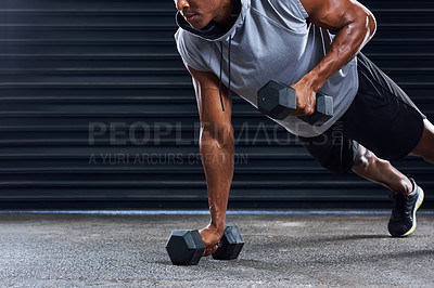 Buy stock photo Shot of a sporty young man working out with dumbbells as part of his exercise routine
