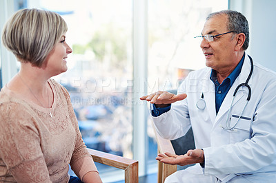 Buy stock photo Shot of a male doctor seeing a patient in his office