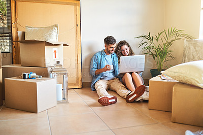 Buy stock photo Shot of a young couple using a laptop while moving into their new home