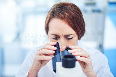 Buy stock photo Shot of a mature scientist using a microscope in a laboratory