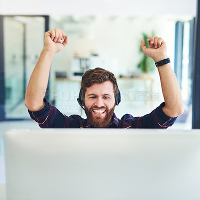 Buy stock photo Shot of a young man cheering at his desk while working together in a call centre